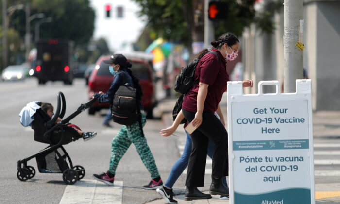 People walk past a sign for a COVID-19 vaccination clinic in Los Angeles, Calif., on Aug. 17, 2021. (Lucy Nicholson/Reuters)