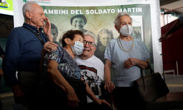A 97 year old retired American soldier Martin Adler poses with Giulio (L), Mafalda (R), and Giuliana Naldi that he saved during WWII at Bologna's airport, Italy, on Aug. 23, 2021. (Antonio Calanni/AP Photo)