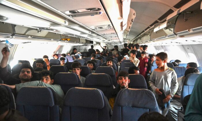 Afghan passengers sit inside a plane as they wait to leave the Kabul airport in Kabul, Afghanistan, on Aug. 16, 2021. (Wakil Kohsar/AFP via Getty Images)