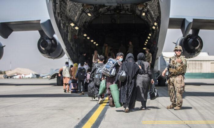 Families begin to board a U.S. Air Force C-17 Globemaster III transport plane during an evacuation at Hamid Karzai International Airport, Afghanistan, on Aug. 23, 2021. (U.S. Marine Corps/Sgt. Samuel Ruiz/Handout via Reuters)