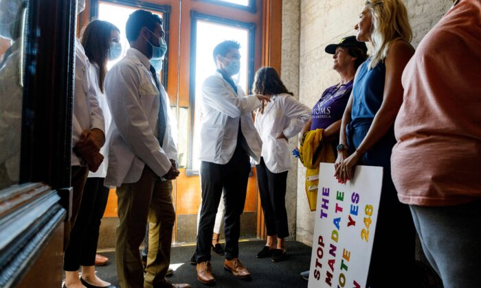 Andrew (C), 24, a medical student from Ohio State University, discusses the Vaccine Choice and Anti-Discrimination Act with people who support the act inside of the Ohio Statehouse in Columbus, Ohio, on Aug. 24, 2021. (Stephen Zenner/AFP via Getty Images)