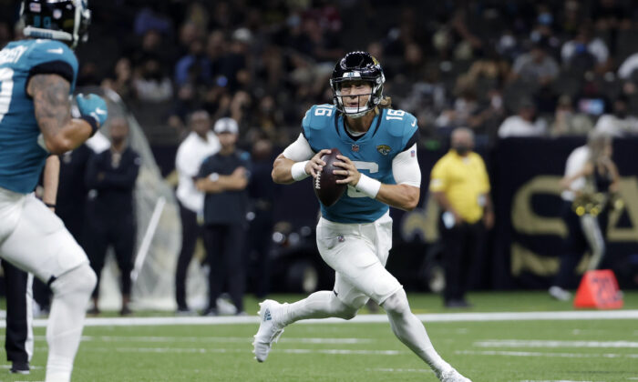 Jacksonville Jaguars quarterback Trevor Lawrence (16) scrambles in the first half of an NFL preseason football game against the New Orleans Saints in New Orleans, La., on Aug. 23, 2021. (Derick Hingle/AP Photo)