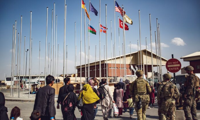 Soldiers assigned to the 82nd Airborne Division escort a group of people to the terminal at Hamid Karzai International Airport in Kabul, Afghanistan, on Aug. 23, 2021. (1st Lt. Mark Andries/U.S. Marine Corps via AP)