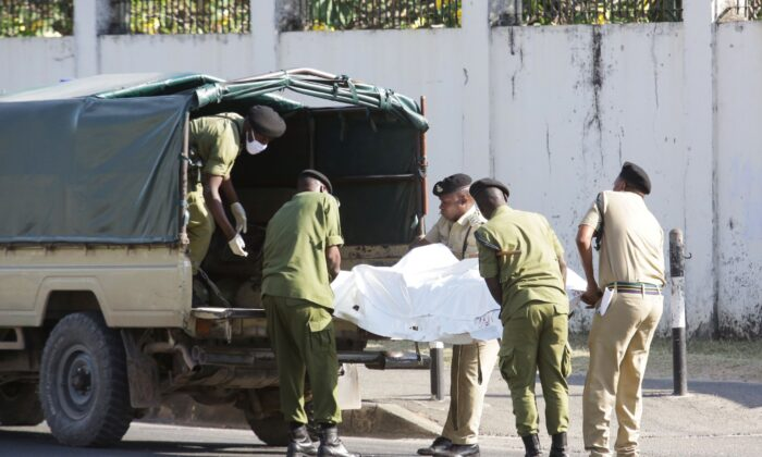 Tanzanian security forces remove the slain body of an attacker who was wielding an assault rifle, outside the French embassy in the Salenda area of Dar es Salaam, Tanzania, on Aug. 25, 2021. (Emmanuel Herman/Reuters)