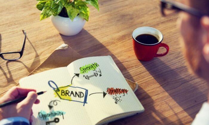 Man reading a book on brands. (Shutterstock.com)