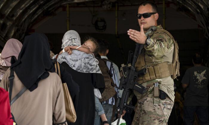 A U.S. Air Force Airman guides evacuees aboard a U.S. Air Force C-17 Globemaster III at Hamid Karzai International Airport in Kabul, Afghanistan, on Aug. 24, 2021. (Senior Airman Taylor Crul/U.S. Air Force via AP)