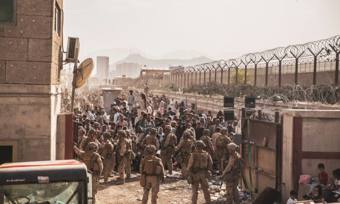 U.S. Marines provide assistance at an Evacuation Control Checkpoint during an evacuation at Hamid Karzai International Airport, Afghanistan, on Aug. 22, 2021. (U.S. Marine Corps/Staff Sgt. Victor Mancilla via Reuters)