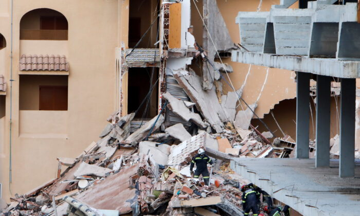 Firefighters work among the debris of a collapsed building in the town of Peniscola, Spain, on Aug. 26, 2021. (Eva Manez/Reuters)