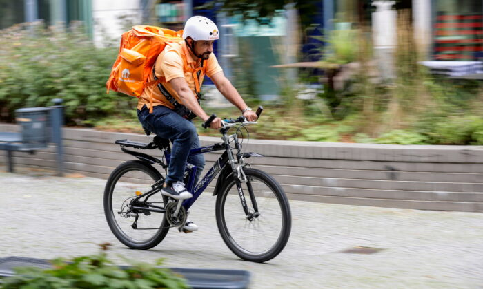 Former Afghan Communication Minister Sayed Sadaat works as a bicycle rider for the food delivery service Lieferando in Leipzig, Germany, August 26, 2021. (Hannibal Hanschke/Reuters)