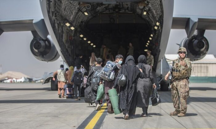 In this image provided by the U.S. Marine Corps, families begin to board a U.S. Air Force Boeing C-17 Globemaster III during an evacuation at Hamid Karzai International Airport in Kabul, Afghanistan, on Aug. 23, 2021. (Sgt. Samuel Ruiz/U.S. Marine Corps via AP)