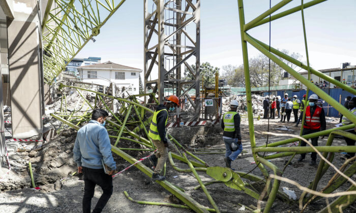 Construction workers observe the wreckage after a crane collapsed at a construction project to build a 14-storey student hostel in Nairobi, Kenya on Aug. 26, 2021. (Brian Inganga/AP Photo)