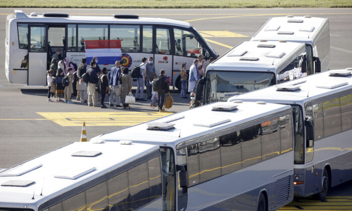 People disembark from a chartered plane and board waiting busses, after being evacuated from Afghanistan, during arrival at Melsbroek Military Airport in Melsbroek, Belgium, on Aug. 25, 2021. (Olivier Matthys/AP Photo)