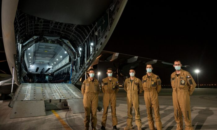 """The crew of an A400M military transport aircraft poses after evacuating people from Kabul as part of the operation """"Apagan"""" at the French military air base 104 of Al Dhafra, near Abu Dhabi, on Aug. 23, 2021. (Bertrand Guay/AFP via Getty Images)"""