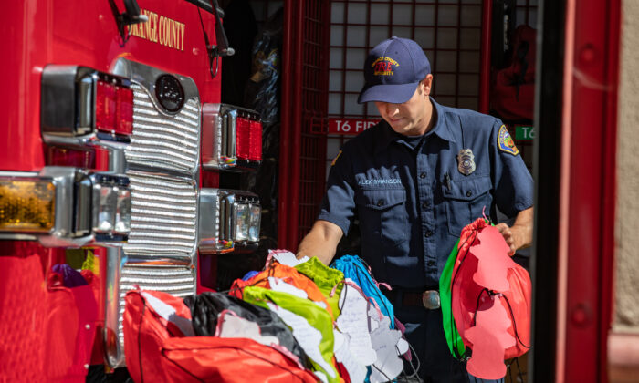 Orange County Fire Authority firefighters recieve gift bags that will be taken to OCFA members fighting statewide fires in Irvine, Calif., on Aug. 26, 2021. (John Fredricks/The Epoch Times)