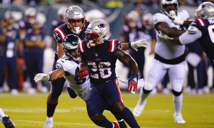 New England Patriots' Sony Michel runs with the ball as Philadelphia Eagles' T.J. Edwards tries to bring him down during the first half of a preseason NFL football game in Philadelphia on Aug. 19, 2021. (AP Photo/Chris Szagola)