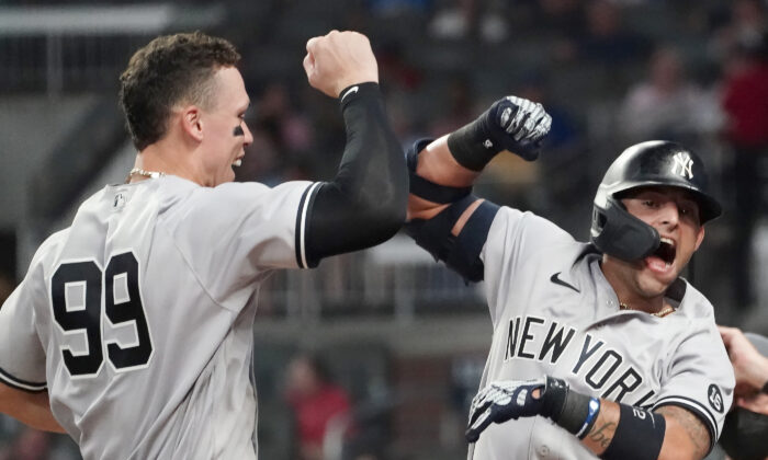 New York Yankees second baseman Rougned Odor (12) celebrates with Aaron Judge (99) after hitting a solo home run in the seventh inning of a baseball game against the Atlanta Braves, in Atlanta, on Aug. 24, 2021. (John Bazemore/AP Photo)