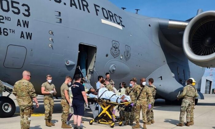 Medical support personnel help an Afghan mother and family off a U.S. Air Force C-17, moments after she delivered a child aboard the aircraft upon landing at Ramstein Air Base, Germany, on Aug. 21, 2021. (U.S. Air Mobility Command via Reuters)