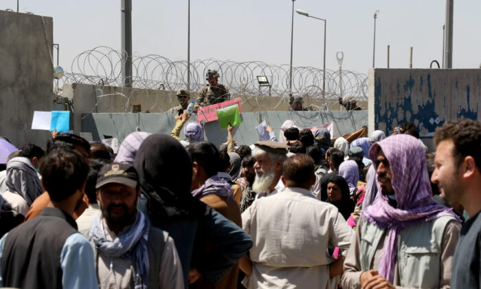Crowds of people show their documents to U.S. troops outside the airport in Kabul, Afghanistan on Aug. 26, 2021. (Stringer/Reuters)