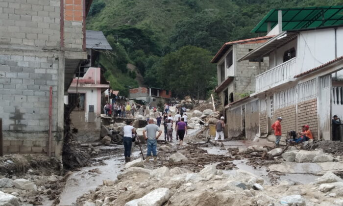 People walk on the street covered in mud following flash flooding in Tovar, Merida State, Venezuela, on Aug. 25, 2021. (Courtesy of Comunicacion Continua/comunicacioncontinua.com/Handout via Reuters)