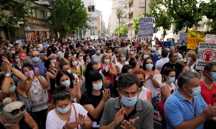Health workers take part in a rally in Athens, on Aug. 26, 2021. (Thanassis Stavrakis/AP Photo)