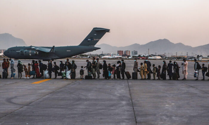 Evacuees wait to board a Boeing C-17 Globemaster III during an evacuation at Hamid Karzai International Airport in Kabul, Afghanistan, on Aug. 23, 2021. (U.S. Marine Corps/Sgt. Isaiah Campbell/Handout via Reuters)