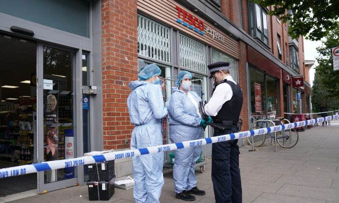 Police officers in forensic suits speak to a colleague outside Tesco Express on Fulham Palace Road, in west London, UK, on Aug. 26, 2021. (Jonathan Brady/PA)