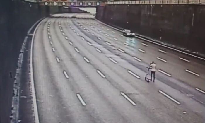 Handout screengrab issued by Central Motorway Police Group/West Midlands Police of a drunken e-scooter rider who was stopped by police while using the Aston Expressway motorway to get home after a night out in Birmingham, UK, on Aug. 22, 2021. (CMPG/PA)