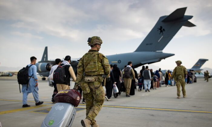 Australian citizens and visa holders prepare to board the Royal Australian Air Force C-17A Globemaster III aircraft, as Australian Army infantry personnel provide security and assist with cargo, at Hamid Karzai International Airport in Kabul, Afghanistan, on Aug. 22, 2021. (SGT Glen McCarthy/ Australia's Department of Defence/Handout via Reuters)