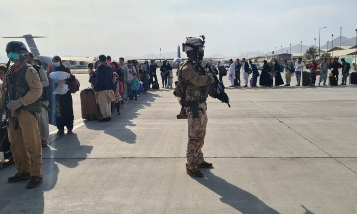 Afghan evacuees queue before boarding Italy's military aircraft C130J during evacuation at Kabul airport, Afghanistan on Aug. 22, 2021. (Italian Ministry of Defence/Handout via Reuters)
