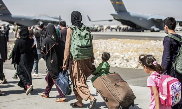 Families walk towards their flight during ongoing evacuations at Hamid Karzai International Airport, Kabul, Afghanistan, on Aug. 24, 2021. (Sgt. Samuel Ruiz/U.S. Marine Corps via AP)
