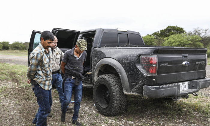 Kinney County Sheriff's Deputy Chris Coplan arrests two illegal aliens after the stolen truck they were traveling in sped through a checkpoint and onto a ranch near Brackettville, Texas, on Aug. 16, 2021. (Charlotte Cuthbertson/The Epoch Times)
