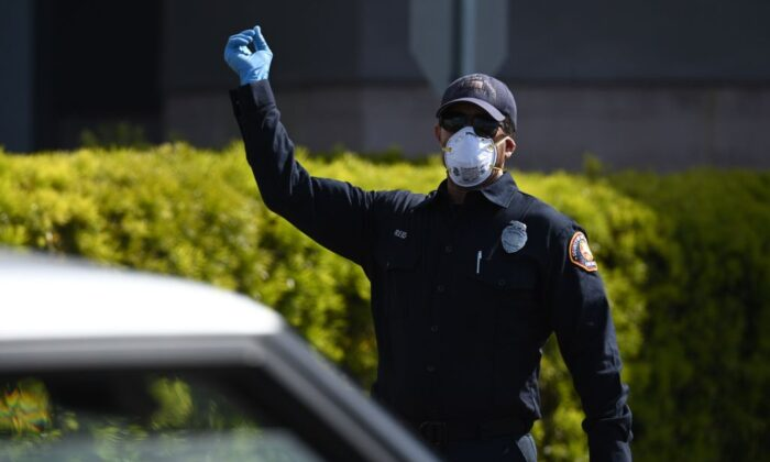 A Los Angeles County firefighter directs traffic at a drive-up coronavirus testing site in Redondo Beach, Calif., on April 3, 2020. (Photo by Robyn Beck / AFP) (Photo by ROBYN BECK/AFP via Getty Images)