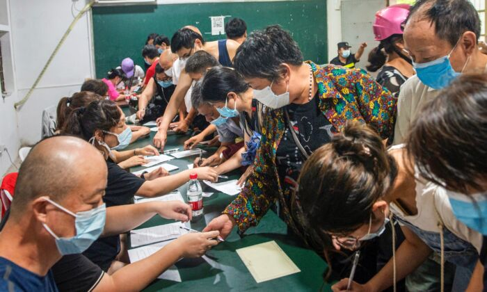 People register information as they prepare to receive the Covid-19 vaccine in Ningbo, in China's eastern Zhejiang Province on Aug. 10, 2021. (STR / AFP)