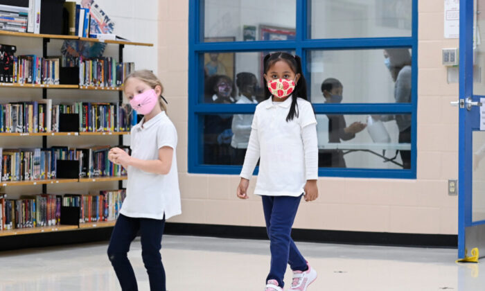 Children arrive in line using physical distancing before getting their picture taken at picture day at St. Barnabas Catholic School during the COVID-19 pandemic in Scarborough, Ont., on Oct. 27, 2020. (THE CANADIAN PRESS/Nathan Denette)