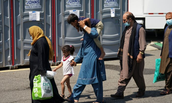 An Afghan man carries a boy on his shoulders upon arrival at a processing center for refugees evacuated from Afghanistan at the Dulles Expo Center near Dulles International Airport in Chantilly, Va., on Aug. 24, 2021. (Kevin Lamarque/Reuters)