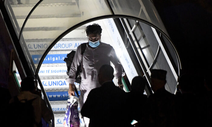 An Afghan man leaves a plane as people arrive from Afghanistan with an evacuation flight at Rinas Airport in Tirana, Albania, on Aug. 27, 2021. (Gent Shkullaku/AFP via Getty Images)