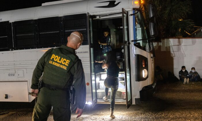 A U.S. Border Patrol agent supervises as immigrants board a bus to a processing center in Roma, Texas on Aug. 14, 2021. (John Moore/Getty Images)