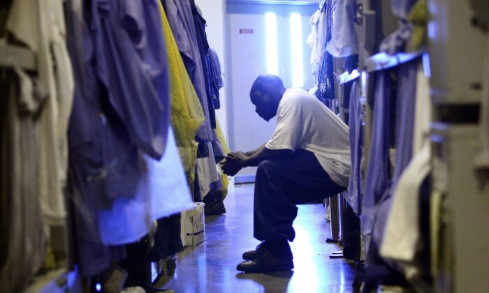 An inmate at the Mule Creek State Prison sits on his bunk bed in a gymnasium that was modified to house prisoners in Ione, Calif., on Aug. 28, 2007. (Justin Sullivan/Getty Images)