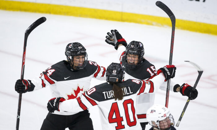 Canada's Melodie Daoust (R), celebrates her goal with teammates Natalie Spooner (L), and Blayre Turnbull during first period IIHF Women's World Championship hockey action against the United States in Calgary, on Aug. 26, 2021.(Jeff McIntosh/The Canada Press)