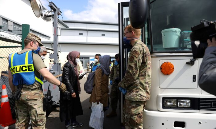 Evacuees from Afghanistan walk from a temporary tent to a bus at Ramstein Air Base in Ramstein-Miesenbach, Germany, on Aug. 26, 2021. (Andreas Rentz/Getty Images)