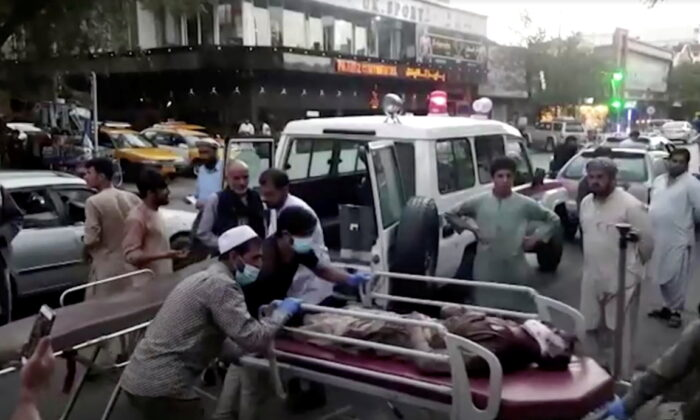 A screen grab shows people carrying an injured person to a hospital after an attack at Kabul airport, in Kabul, Afghanistan, on Aug. 26, 2021. (Reuters TV/1TV/Handout via Reuters)