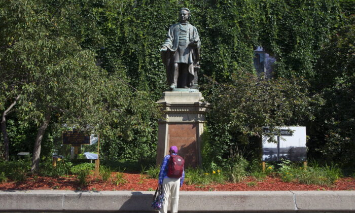 A passer-by looks at a statue of Egerton Ryerson outside Toronto's Ryerson University on July 6, 2017. The statue has since been toppled and will not be replaced, and Ryerson's board of governors has now approved a name change for the university. (The Canadian Press/Chris Young)