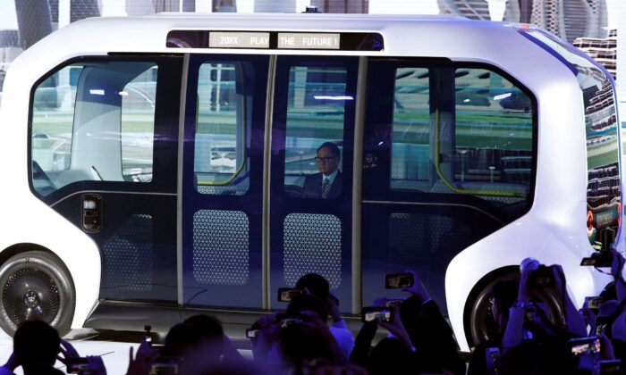 Toyota Motor Corporation President Akio Toyoda, arrives in their e-Palette autonomous concept vehicle to give his presentation at the Tokyo Motor Show, in Tokyo, Japan, on Oct. 23, 2019. (Edgar Su/File/Reuters)
