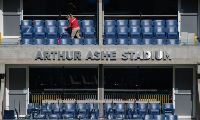 A worker sweeps a seating area at the Arthur Ashe stadium ahead of the 2021 U.S. Open Tennis tournament at the Billie Jean King National Tennis Center in Queens, New York, on Aug. 24, 2021. (Ed Jones/AFP via Getty Images)