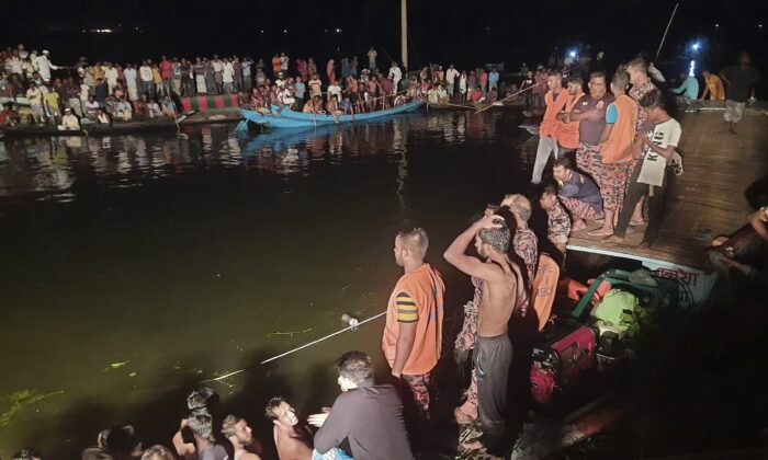 People watch rescue work after a passenger boat carrying more than 100 people sank after a collision in a large pond in Brahmanbaria district, Bangladesh, on Aug. 27, 2021. (AP Photo)