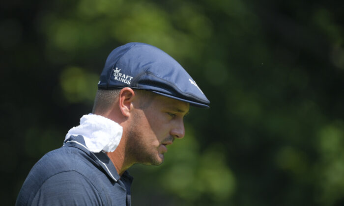 Bryson DeChambeau wears a towel on his neck during high temperatures at the BMW Championship golf tournament in Caves Valley Golf Club in Owings Mills, Md.on Aug. 27, 2021. (AP Photo/Nick Wass)