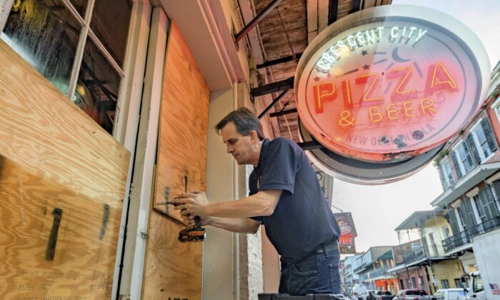 Michael Richard of Creole Cuisine Restaurant Concepts boards up Crescent City Pizza on Bourbon Street in the French Quarter before landfall of Hurricane Ida in New Orleans, on Aug. 28, 2021. (Matthew Hinton/AP Photo)