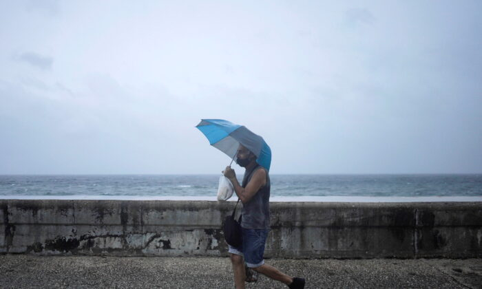 A man protects himself from wind and rain as he walks at the seafront Malecon while Hurricane Ida approaches the island, in Havana, Cuba, on Aug. 27, 2021. (Alexandre Meneghini/Reuters)