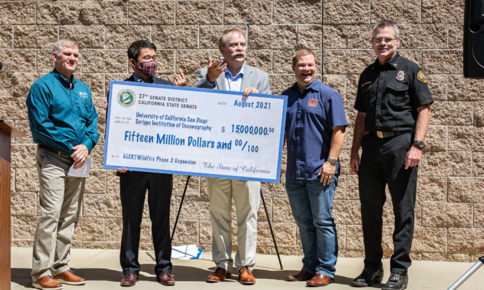 Senator Dave Min presents a check for $15,000,000 to the Orange County Fire Authority at Fire Station 1 in Tustin, Calif., on Aug. 27, 2021. (John Fredricks/The Epoch Times)