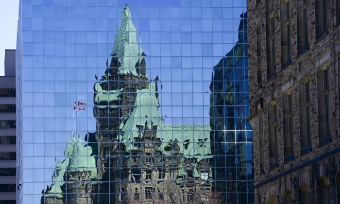 The Confederation Building reflects off the windows of a building in downtown Ottawa, on April 7, 2020. (The Canadian Press/Sean Kilpatrick)